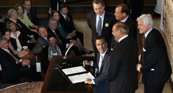 Mitt Romney signing Massachusetts' health reform bill in 2006.