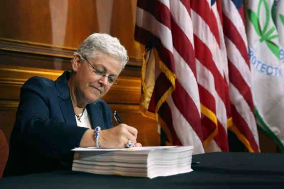 EPA administrator Gina McCarthy signing new regulations on carbon pollution.